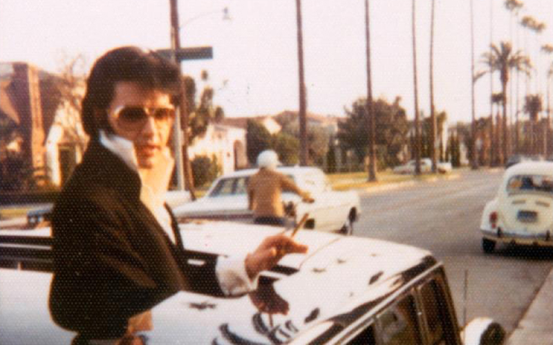Elvis Presley peeping out the sunroof of a 1969 Mercedes-Benz 600 limousine while in Los Angeles